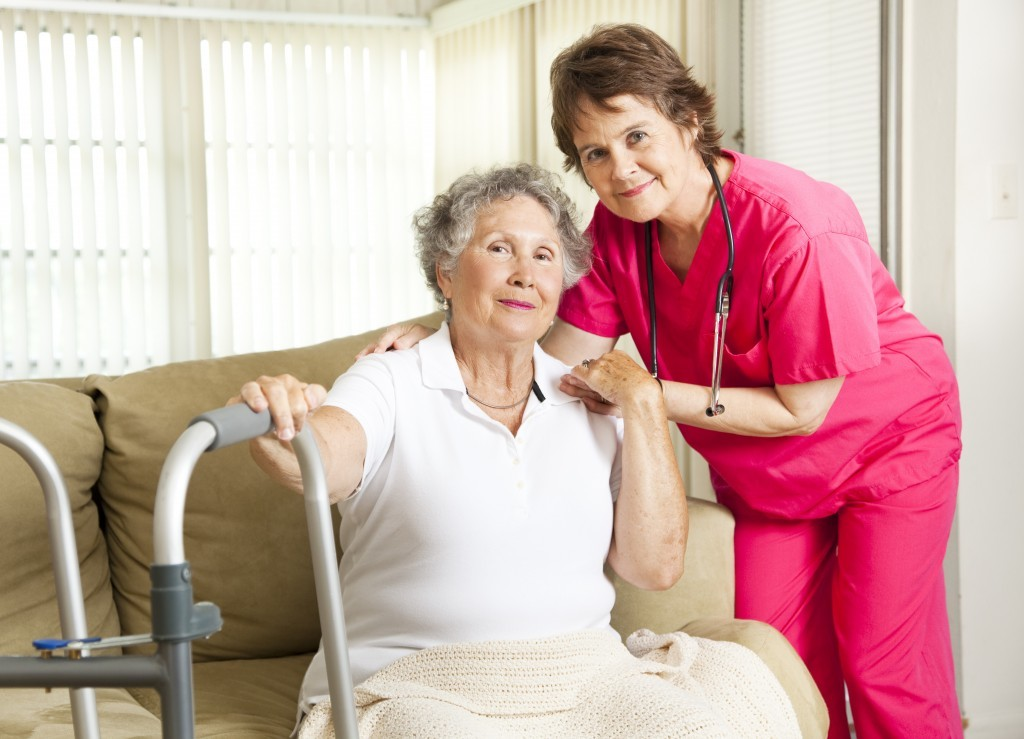 Caregiver in pink helping senior woman with walker
