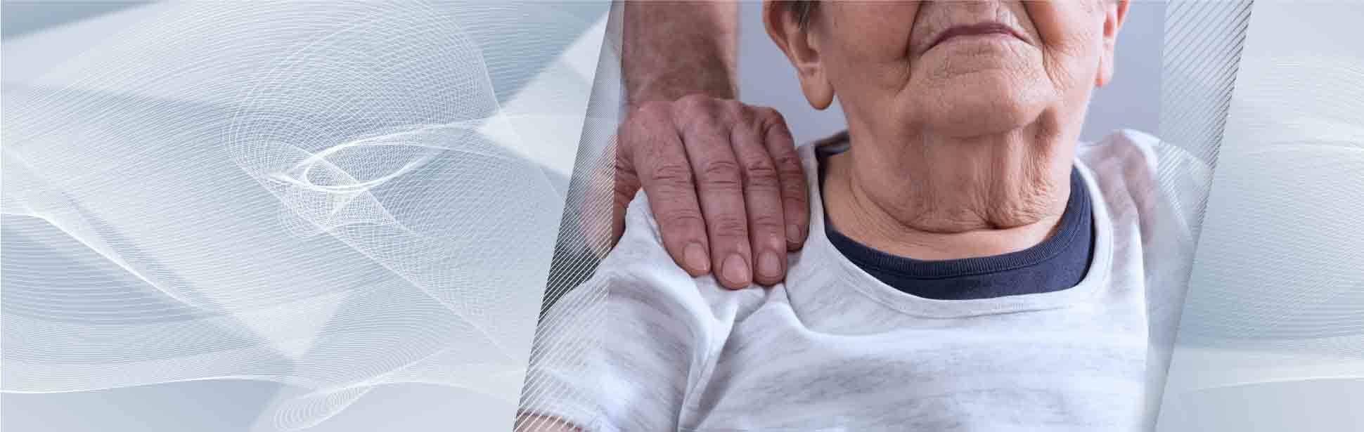Adult day care caregiver with reassuring hand on seniors shoulder