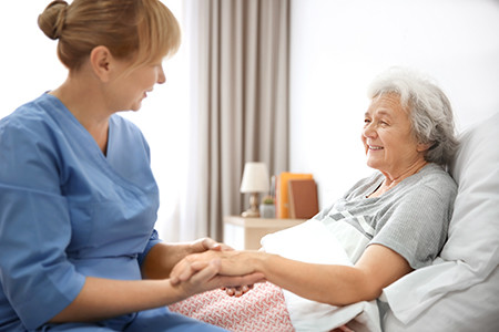Care Services helping senior woman sit up in bed, smiling