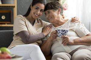Caring person and happy elderly woman drinking tea at home