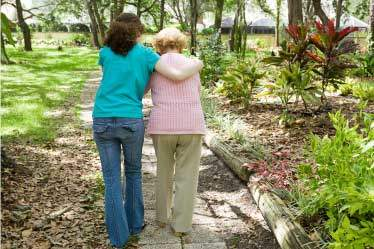 Caregiver helping an elderly woman walk on garden path