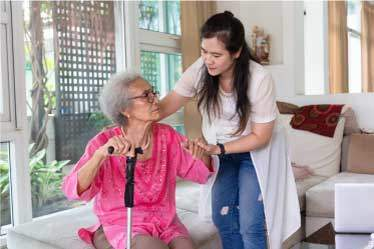 Caregiver helping elderly woman with cane stand up