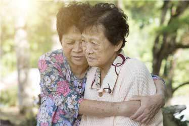 Elderly asain woman comforting a friend