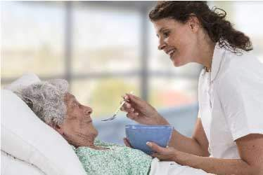 Hospice nurse smiling, while feeding patient soup