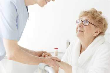 Hospice nurse holding seated senior woman's hands