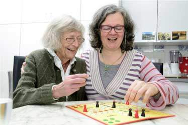 Mom and daughter having fun playing a board game