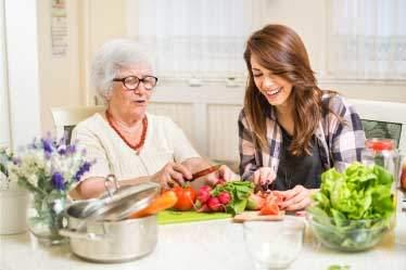 Grandma and grand daughter preparing salad