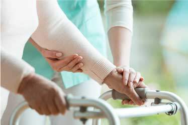 Nurse assisting an elderly woman with a walker