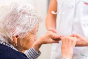 Elderly woman seated, holding nurses hands