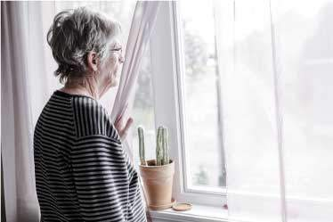 Senior woman appearing depressed, looking out her window of assisted living facility