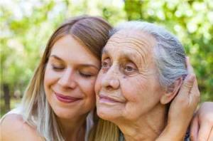 Close up picture of senior disabled woman with loving granddaughter in the garden